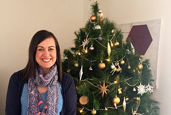 Bianca from the assured tree care team in from of a christmas tree