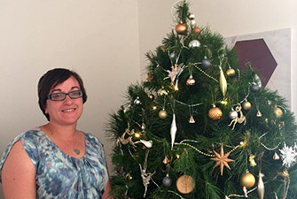 Kim from the assured tree care team in from of a christmas tree